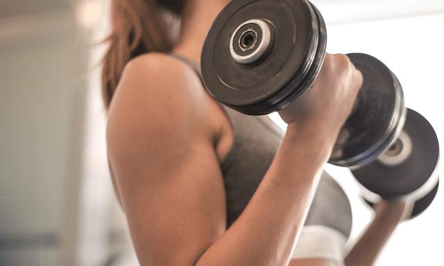 sports woman using dumbells